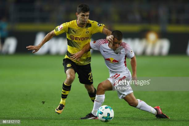 Christian Pulisic of Dortmund fights for the ball with Diego Demme of Leipzig during the Bundesliga match between Borussia Dortmund and RB Leipzig at...