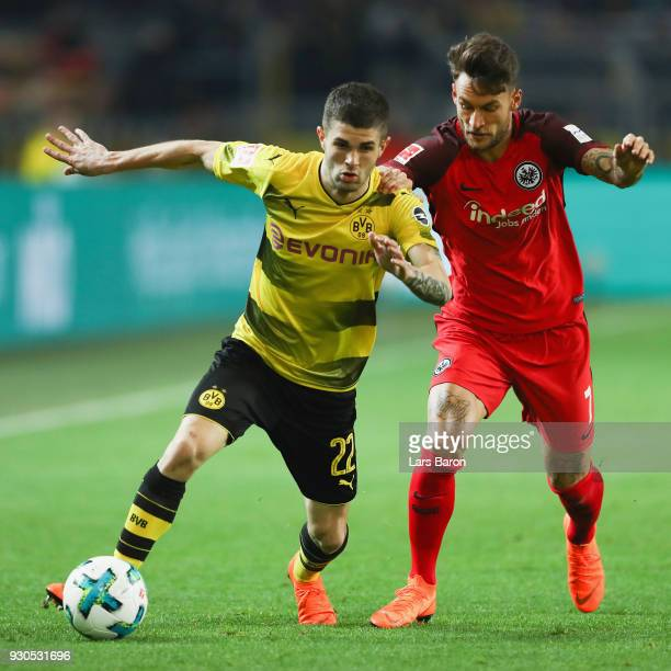Christian Pulisic of Dortmund is challenged by Danny Blum of Frankfurt during the Bundesliga match between Borussia Dortmund and Eintracht Frankfurt...