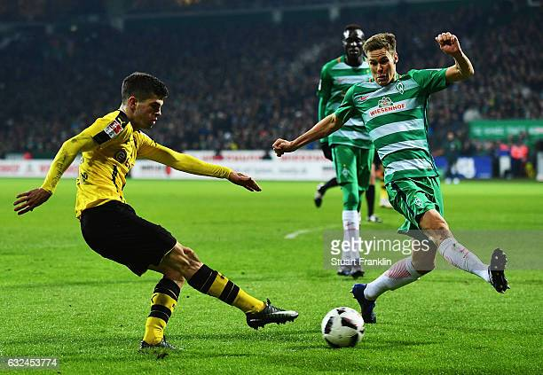 Christian Pulisic of Dortmund is challenged by Florian Kainz of Bremen during the Bundesliga match between Werder Bremen and Borussia Dortmund at...