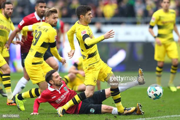 Christian Pulisic of Dortmund is challenged by Julian Korb of Hannover during the Bundesliga match between Hannover 96 and Borussia Dortmund at...