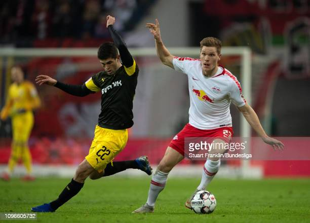 Christian Pulisic of Dortmund is challenged by Marcel Halstenberg of Leipzig during the Bundesliga match between RB Leipzig and Borussia Dortmund at...