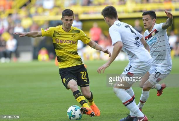 Christian Pulisic of Dortmund Panagiotis Retsos of Leverkusen and Charles Aranguiz of Leverkusen battle for the ball during the Bundesliga match...