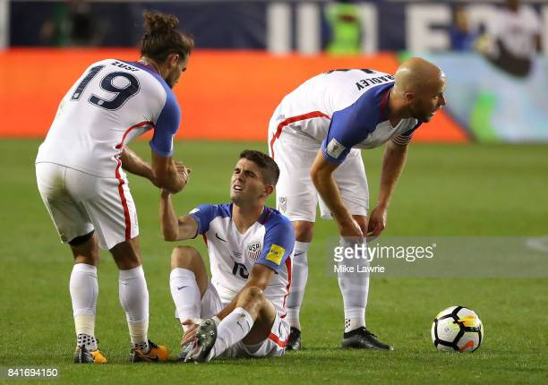 Christian Pulisic of the United States is helped up by teammate Graham Zusi after a foul in the first half against Costa Rica during the FIFA 2018...