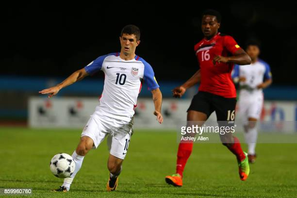 Christian Pulisic of the United States mens national team runs with the ball as Levi Garcia of Trinidad and Tobago chases him down during the FIFA...