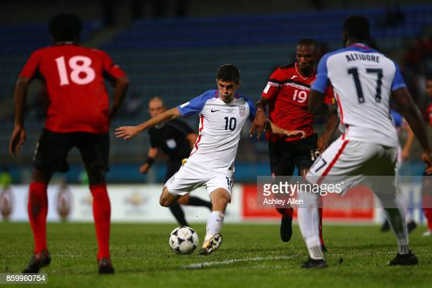 Christian Pulisic of the United States mens national team scores a goal as Kaven George of Trinidad and Tobago attempts to block the shot during the...