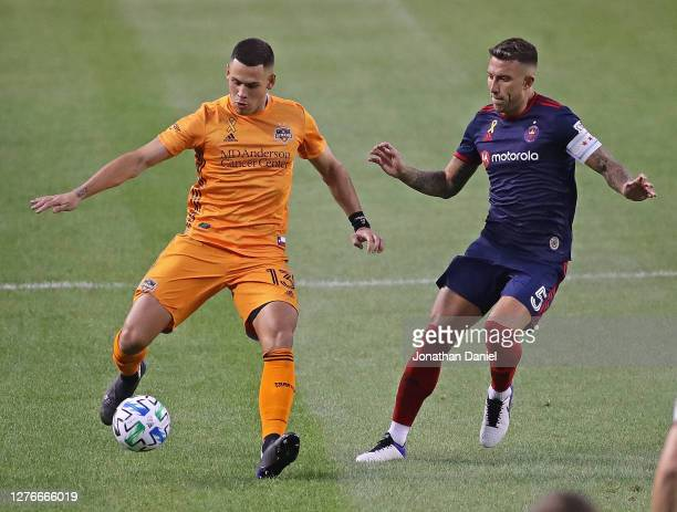 Christian Ramirez of Houston Dynamo looks to pass under pressure from Francisco Calvo of Chicago Fire FC at Soldier Field on September 23, 2020 in...