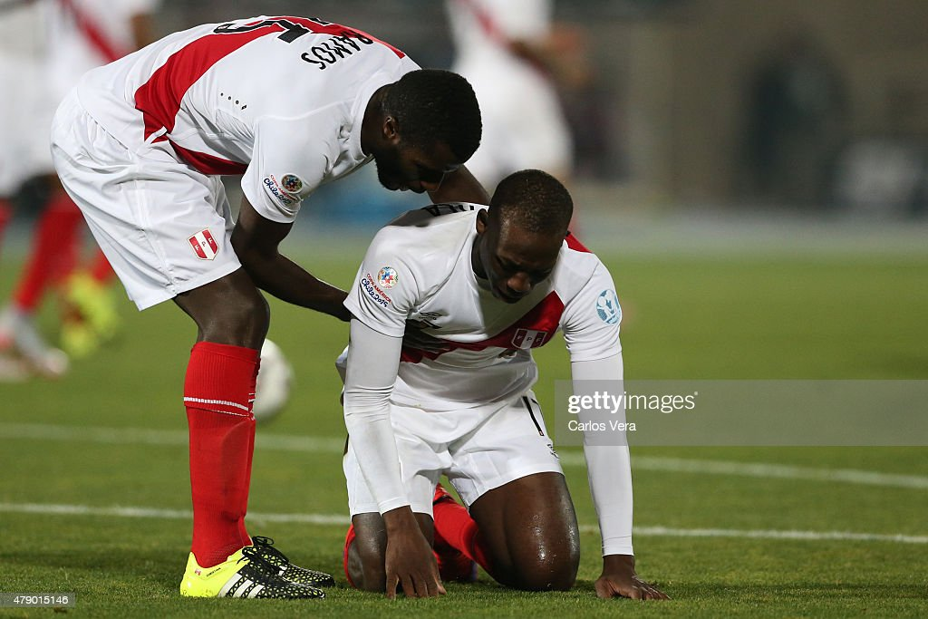 Christian Ramos helps his teammate Luis Advincula of Peru after the 2015 Copa America Chile Semi Final match between Chile and Peru at Nacional Stadium on June 29, 2015 in Santiago, Chile.