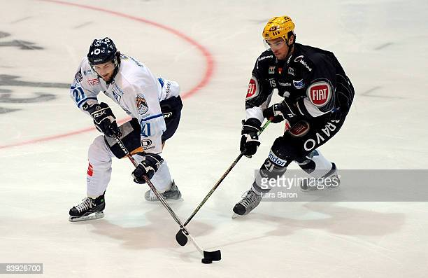 Christian Retzer of Straubing is challenged by Josh Langfeld of Frankfurt during the DEL match between Frankfurt Lions and Straubing Tigers at the...