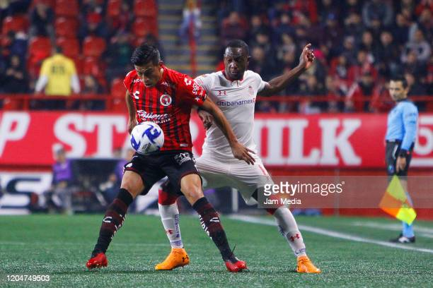 Christian Rivera of Tijuana struggles for the ball against Anibal Chala of Toluca during the 5th round match between Tijuana and Toluca as part of...
