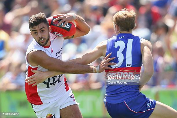Christian Salem of the Demons avoids a tackle by Bailey Dale of the Bulldogs during the 2016 AFL NAB Challenge match between the Western Bulldogs and...