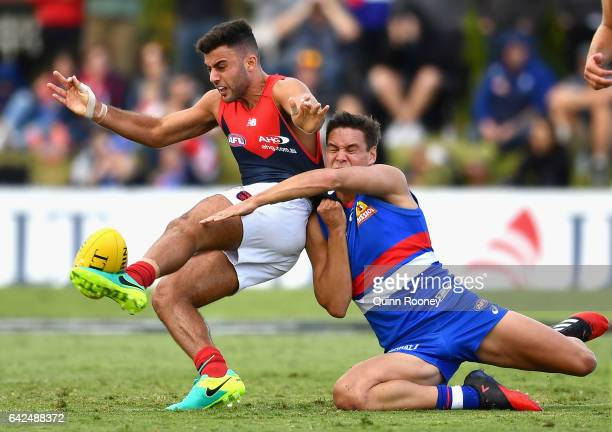 Christian Salem of the Demons kicks whilst being tackled by Lukas Webb of the Bulldogs during the 2017 JLT Community Series match between the Western...