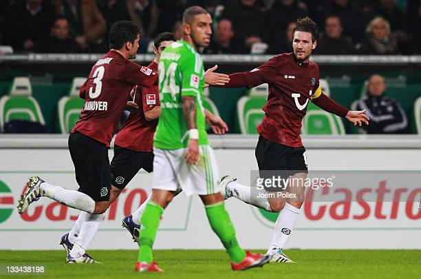 Christian Schulz of Hannover celebrates awith his team mates after scoring his team's first goal during the Bundesliga match between VfL Wolfsburg...