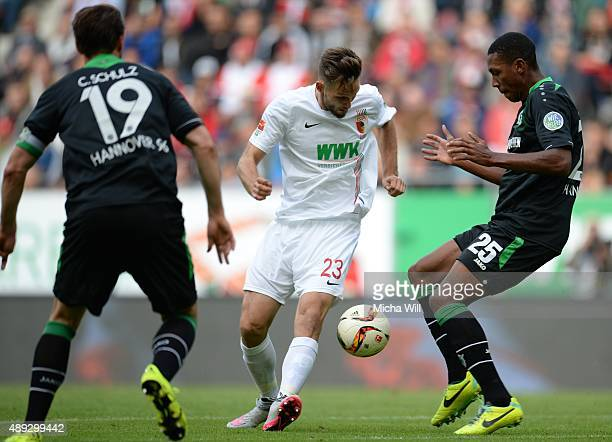 Christian Schulz of Hannover Tim Matavz of Augsburg and Marcelo of Hannover compete for the ball during the Bundesliga match between FC Augsburg and...