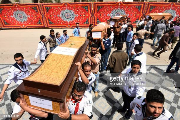 Christian scouts carry the coffins of victims of the blast at the Coptic Christian Saint Mark's church in Alexandria the previous day during a...