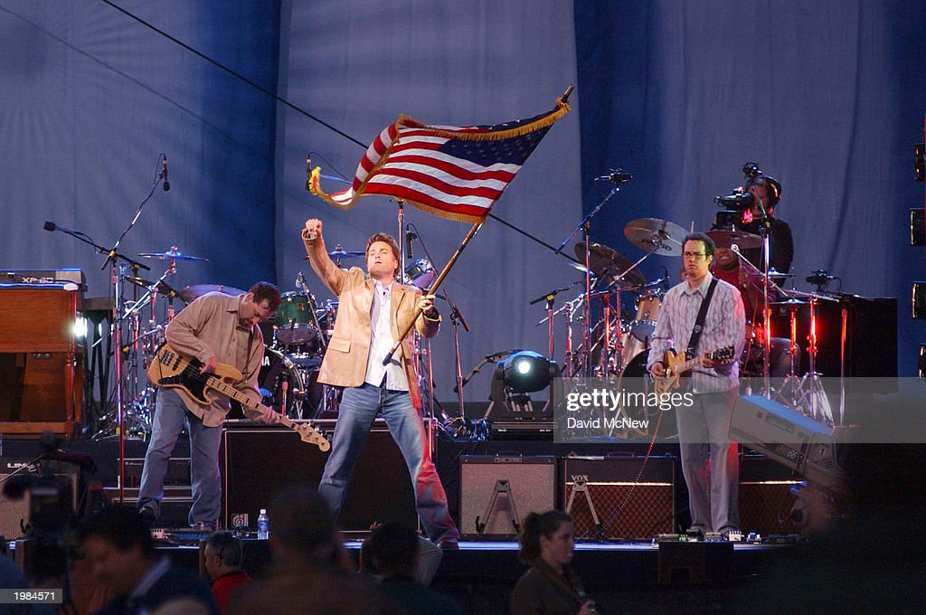 Christian singer Michael W. Smith waves an American flag while singing patriotic songs during the last mission to California for America's best known evangelist, 84-year-old Billy Graham, on May 8, 2003 to San Diego, California. Some 54,000 people attended tonight's service which is expected to total 200,000 over the four-night event as thousands convert to Christianity.