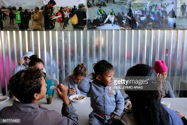 TOPSHOT Christian sits next to his mother and other Central American migrants during the 'Migrant Via Crucis' caravan as they have breakfast at...