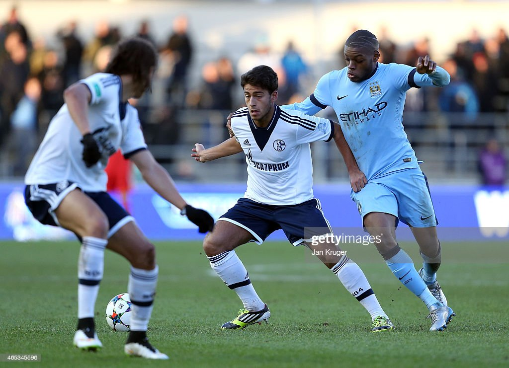 Christian Sivodedov of FC Schalke 04 battles with Oliver Ntcham of Manchester City FC during the UEFA Youth League Round of 16 match between Manchester City FC and FC Schalke 04 at City Football Academy on February 24, 2015 in Manchester, England.