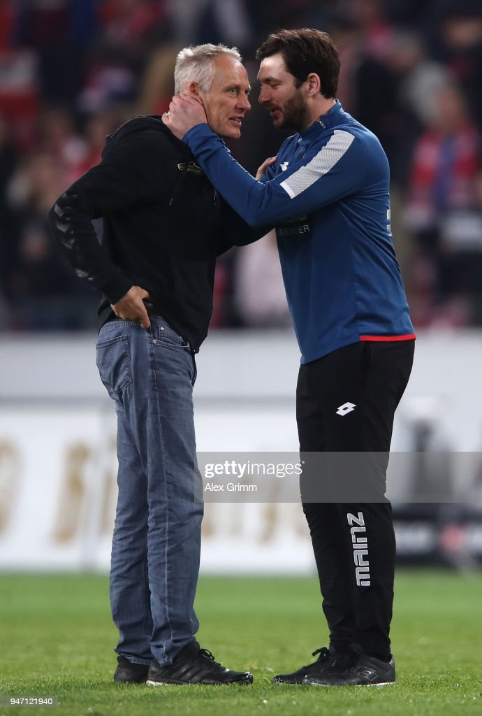 Christian Streich, head coach of Freiburg is consoled by Sandro Schwarz; head coach of Mainz after the Bundesliga match between 1. FSV Mainz 05 and Sport-Club Freiburg at Opel Arena on April 16, 2018 in Mainz, Germany.