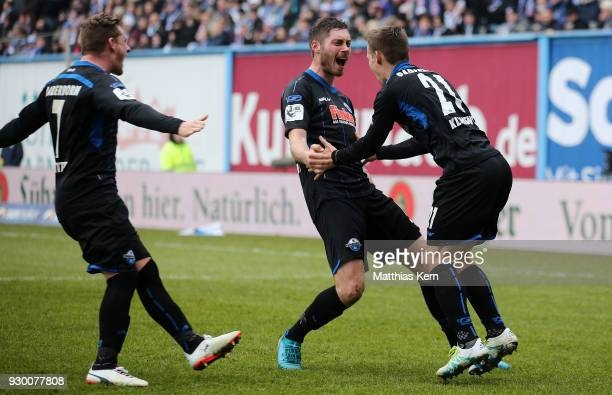 Christian Strohdiek of Paderborn jubilates with team mates after scoring the fived goal during the 3Liga match between FC Hansa Rostock and SC...