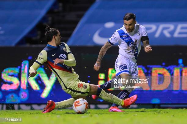 Christian Tabó of Puebla competes for the ball against Jorge Sánchez of America during the 9th round match between Puebla and America as part of the...