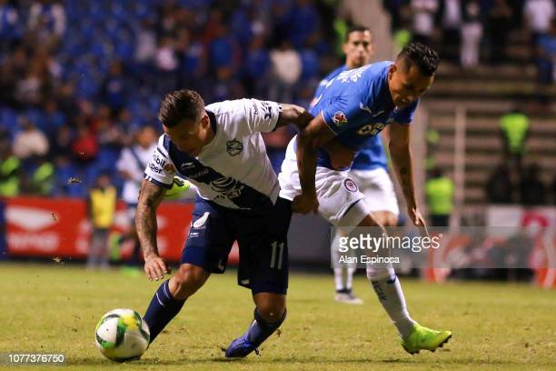 Christian Tabo of Puebla fights for the ball with Yoshimar Yotun of Cruz Azul during the 1st round match between Puebla and Cruz Azul as part of the...