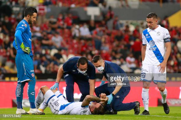 Christian Tabo of Puebla receives medical attention after suffering an injury during the quarterfinals first leg match between Atlas and Puebla as...
