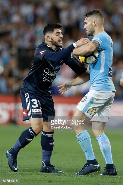Christian Theoharous of the Victory and Bart Schenkeveld of Melbourne City wrestle for the ball during the round 12 ALeague match between Melbourne...