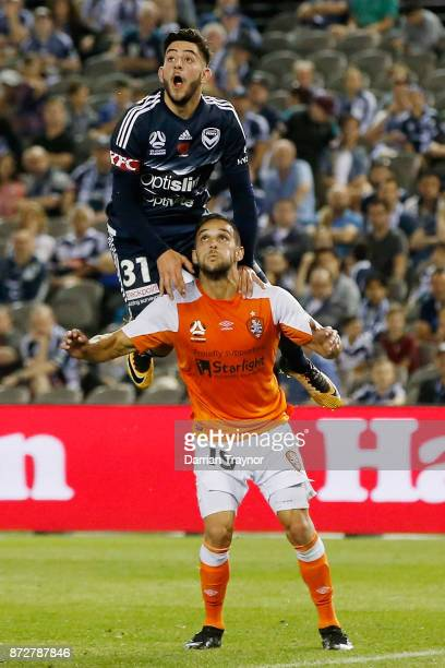 Christian Theoharous of the Victory jumps over Jack Hingert of the Roar in an attempt to head the ball during the round six ALeague match between the...