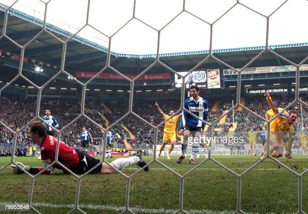 Christian Tiffert of Duisburg celebrates his first goal while Mathias Hain and Andre Mijatovic of Bielefeld look dejected during the Bundesliga match...
