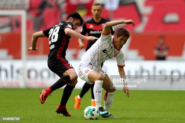 Christian Traesch of Ingolstadt challenges Genki Haraguchi of Duesseldorf during the Second Bundesliga match between Fortuna Duesseldorf and FC...