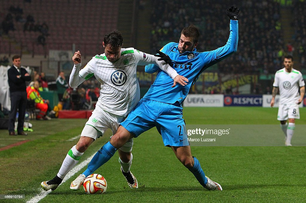 Christian Trasch of VfL Wolfsburg competes for the ball with Davide Santon of FC Internazionale Milano during the UEFA Europa League Round of 16 match between FC Internazionale Milano and VfL Wolfsburg at Stadio Giuseppe Meazza on March 19, 2015 in Milan, Italy.