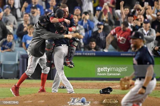 Christian Vazquez and David Price embrace Chris Sale of the Boston Red Sox to celebrate their 51 win over the Los Angeles Dodgers in Game Five to win...