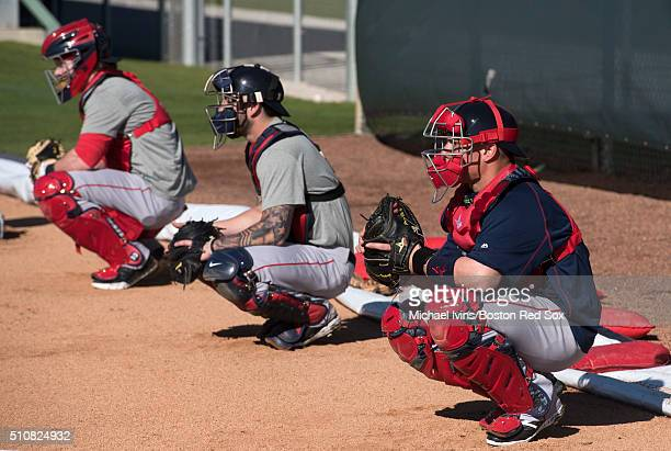 Christian Vazquez of the Boston Red Sox catches alongside Blake Swihart center and Ryan Hanigan during a Spring Training workout at Fenway South in...