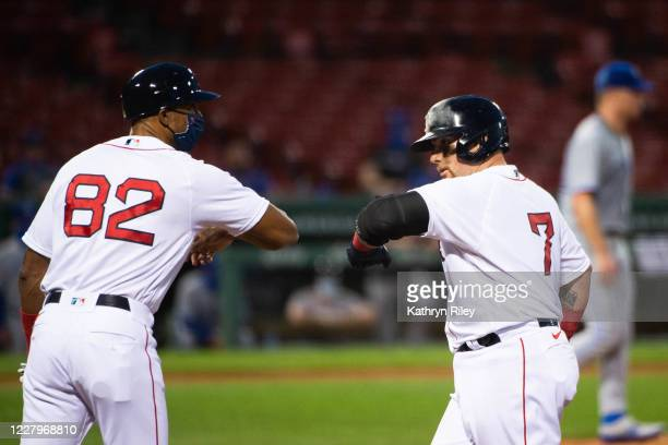 Christian Vazquez of the Boston Red Sox celebrates with first base coach Tom Goodwin after hitting an RBI single in the second inning against the...