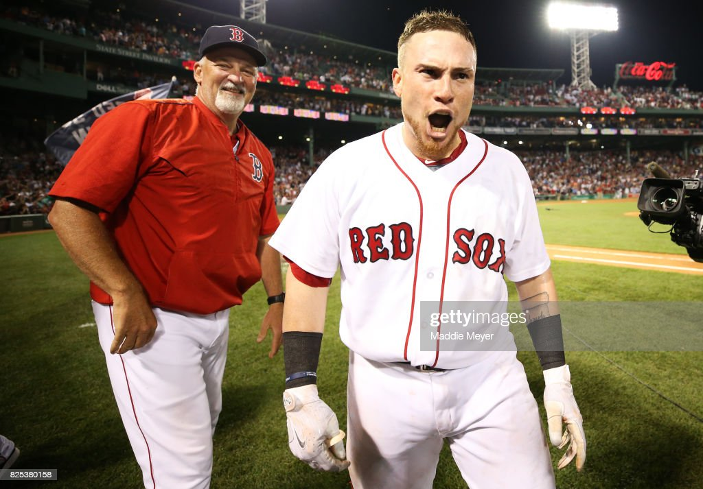 Christian Vazquez #7 of the Boston Red Sox celebrates with pitching coach Carl Willis after hitting a three run homer in the ninth inning to defeat the Cleveland Indians 12-10 at Fenway Park on August 1, 2017 in Boston, Massachusetts.