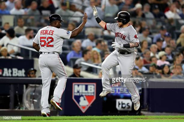 Christian Vazquez of the Boston Red Sox celebrates with third base coach Carlos Febles of the Boston Red Sox after hitting a solo home run in the...