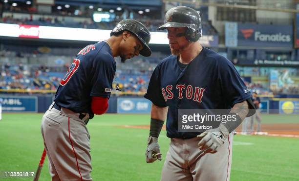 Christian Vazquez of the Boston Red Sox is congratulated by Mookie Betts after his sacrifice fly in the 11th inning of a baseball game against the...