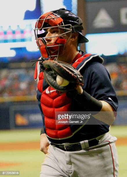 Christian Vazquez of the Boston Red Sox jogs back to the dugout holding the ball he caught on a foul tip for the third out during the game against...