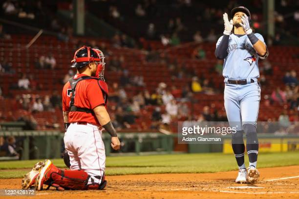 Christian Vazquez of the Boston Red Sox looks on as Bo Bichette of the Toronto Blue Jays reacts as he crosses home plate after hitting a solo home...