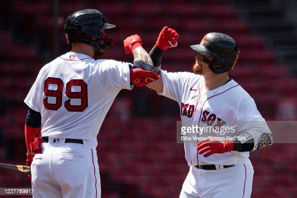Christian Vazquez of the Boston Red Sox reacts with Alex Verdugo after hitting a solo home run during second the inning of a game against the...