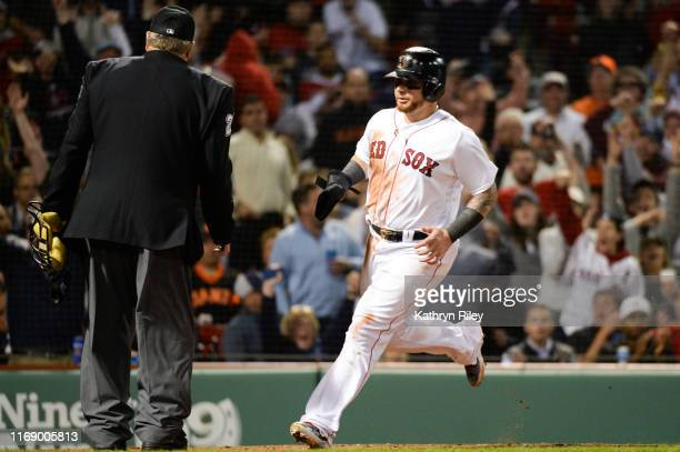 Christian Vazquez of the Boston Red Sox scores the game tying run off of a wild pitch in the sixth inning against the San Francisco Giants at Fenway...
