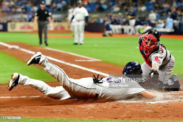 Christian Vazquez of the Boston Red Sox tags Travis d'Arnaud of the Tampa Bay Rays out at home plate during the third inning of a baseball game at...