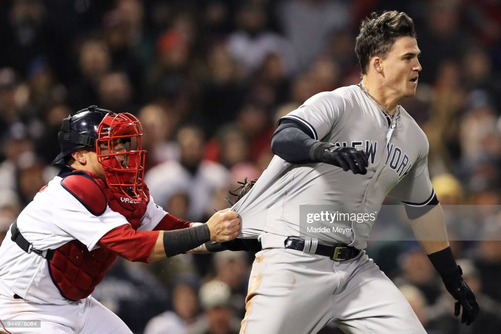 Christian Vazquez #7 of the Boston Red Sox tries to hold back Tyler Austin #26 of the New York Yankees as he storms the pitchers mound after being stuck by a pitch thrown by Joe Kelly #56 during the seventh inning at Fenway Park on April 11, 2018 in Boston, Massachusetts.