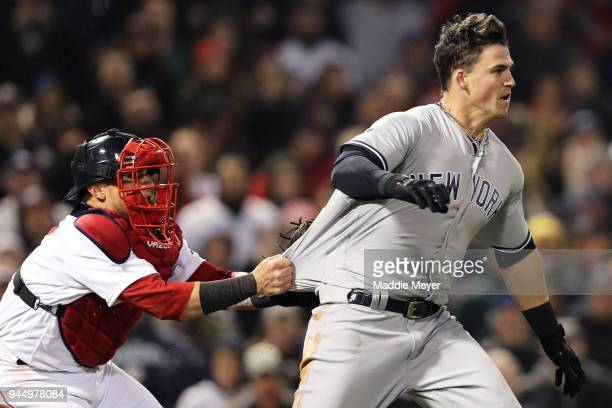 Christian Vazquez of the Boston Red Sox tries to hold back Tyler Austin of the New York Yankees as he storms the pitchers mound after being stuck by...