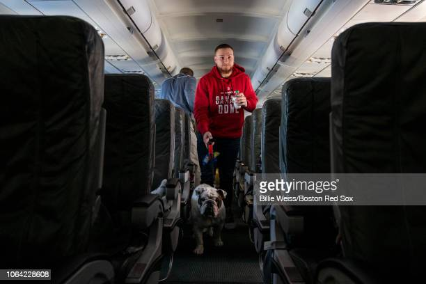 Christian Vazquez of the Boston Red Sox walks down the aisle with his dog Champs during a trip from Boston Massachusetts to Caguas Puerto Rico on...