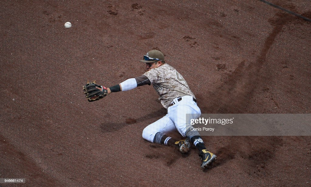 Christian Villanueva #22 of the San Diego Padres can't make a sliding catch on the foul ball hit by Brandon Belt #9 of the San Francisco Giants during the second inning of a baseball game at PETCO Park on April 15, 2018 in San Diego, California. All players are wearing #42 in honor of Jackie Robinson Day.