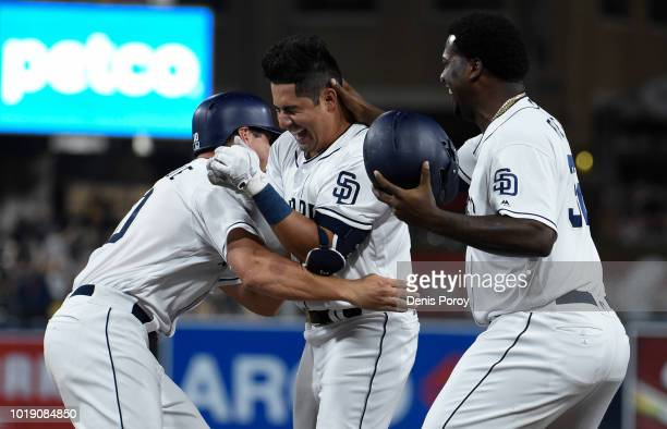 Christian Villanueva of the San Diego Padres celebrates his walk off single with Franmil Reyes and Hunter Renfroe during the ninth inning of a...