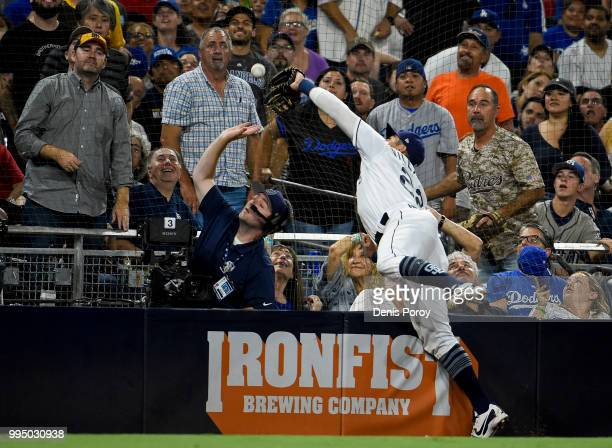 Christian Villanueva of the San Diego Padres dives into the netting as he chases a foul ball hit by Cody Bellinger of the Los Angeles Dodgers during...