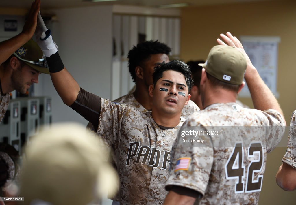 Christian Villanueva #22 of the San Diego Padres is congratulted after hitting a solo home run during the fifth inning of a baseball game against the San Francisco Giants at PETCO Park on April 15, 2018 in San Diego, California. All players are wearing #42 in honor of Jackie Robinson Day.