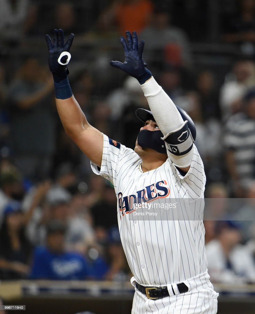 Christian Villanueva #22 of the San Diego Padres points skyward after hitting a solo home run during the seventh inning of a baseball game against the Los Angeles Dodgers at PETCO Park on July 11, 2018 in San Diego, California.